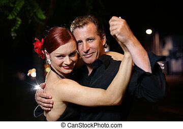 Tango - Happy young adult couple dancing outdoors at night,...