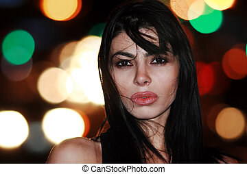 Portrait of a beautiful young brunette woman at night