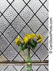 Yellow flowers bouquet at vitrage window