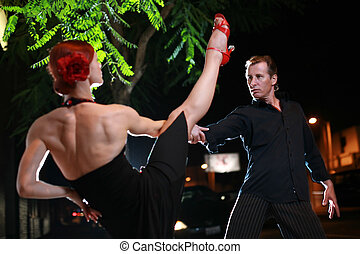Couple dancing hot latin dance on a street at night