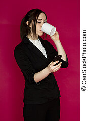 Multi-tasking business woman - Young business woman drink a...