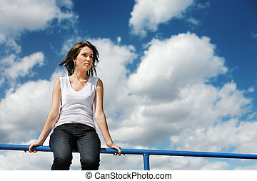 Beautiful young woman sitting on a border over cloudy blue...