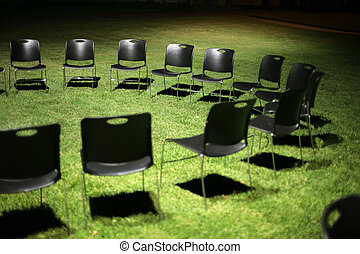 Circle of black chairs on green grass at night. Shallow DOF.