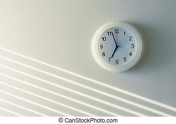 White clock on white wall background