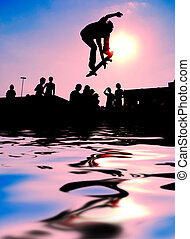 Skateboarder jumping over the water at sunset.