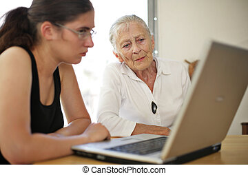 Grandmother and granddaughter with laptop.