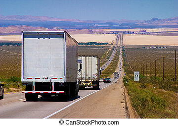 Interstate delivery trucks on a highway.