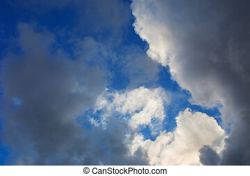 Dramatic clouds, blue sky behind