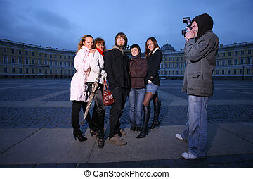Photographer taking a fashion photo of a small group of...
