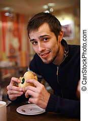Young man eating burger in fast food restaurant. Shallow...