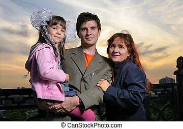 Portrait of young happy family with child outdoors at sunset