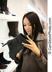 Beautiful woman shopping at fashion shoe store