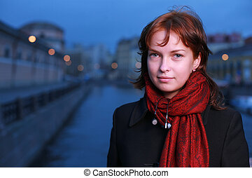 Portrait of a young redhead woman standing by a canal in St....