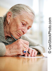 Portrait of a senior lady writing Close-up, shallow DOF