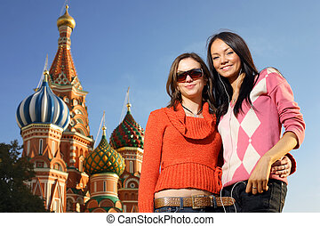 Two beautiful young women next to Saint Basils Cathedral in...
