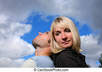Man resting head on woman's shoulder, looking at the sky.