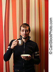 Cool young man with cup of tea or coffee