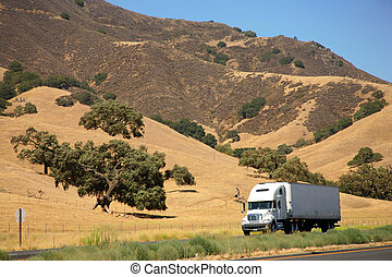 Truck on freeway - American truck speeding on freeway at...