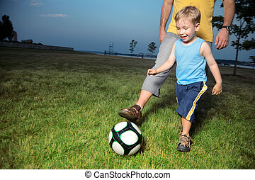 Boy playing football with his dad outdoors