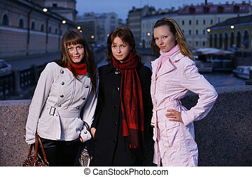 Three young girls in a twilight city. St. Petersburg,...