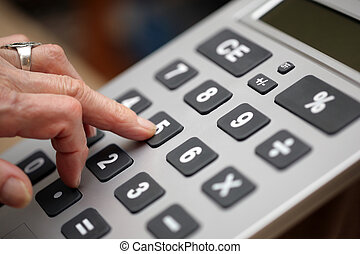 Senior woman fingers pressing keys on big calculator