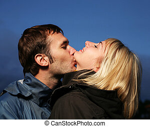 Young couple kissing outdoors at dusk