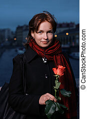 Portrait of a young redhead woman with fresh red rose in St. Petersburg, Russia.