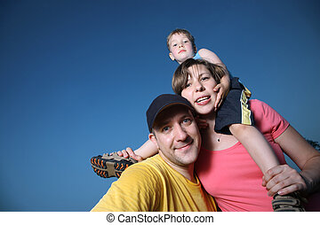 Happy family outdoors over blue sky