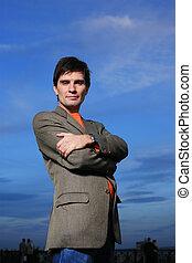 Confident business man over blue sky