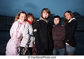 Group of five trendy young people standing in a city square