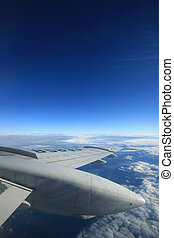 Airplane wing and blue sky. Lots of copy-space available.