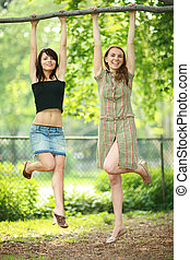 Two beautiful girls hanging on tree branch in park, laughing...