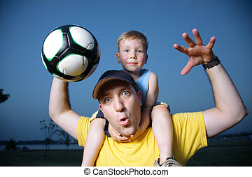 Dad and son playing football outdoors