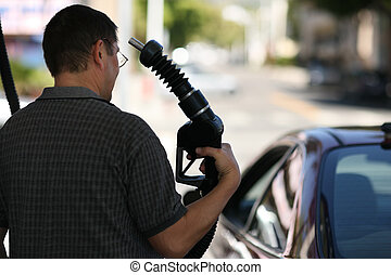 Man pointing gas nozzle to his head. Shallow DOF.