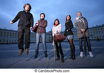 Group of five trendy young people jumping in a city square