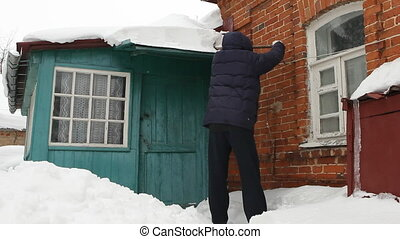 Man clearing snow from roof eaves