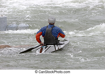 White Water Slalom - A canoeist paddling through fast...