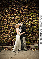 Romantic Kiss in Front of Ivy Wall