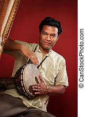 Young Tabla Player - Handsome Indian man on maroon...