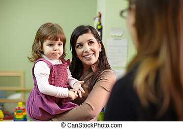 Educator and mother with little girl at school - Caucasian...