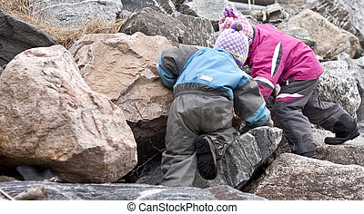 Children searching for treasures between large rocks