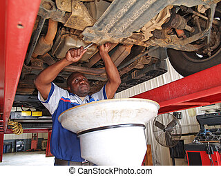 Mechanic Performing an Oil Change - Auto mechanic performing...