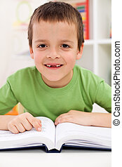 Happy elementary school boy practice reading