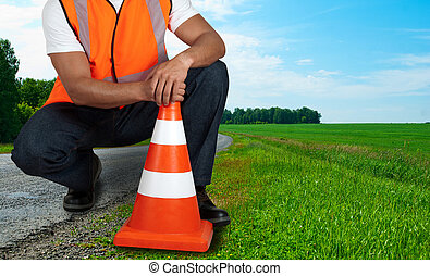 road worker closeup with orange posts at road