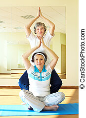 Yoga practice - Portrait of two aged females doing yoga...