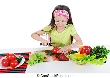 Little girl cut tomatoes at the table. Isolated on white...