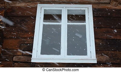 Slow motion of snowing against the window of an old wooden...