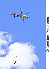 Rescue helicopter rescuing person by airlifting dangling on...