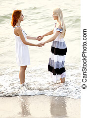 Two beautiful young girlfriends jumping on the beach of...