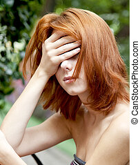 Sad red-haired girl at garden.